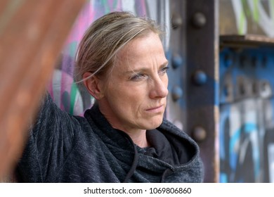 Thoughtful blond woman with a contemplative look standing against a colorful graffiti covered wall staring to the side in a close up portrait