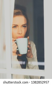 Thoughtful blond woman with cup of coffee looking through the window.