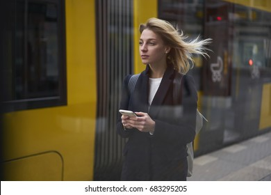 Thoughtful blonde female tourist using online maps on smartphone for strolling on city street  searching right direction, attractive traveler waiting for public transport standing on bus stop