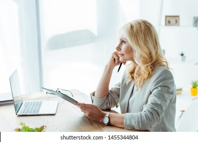 thoughtful blonde woman holding clipboard and pen near laptop in office