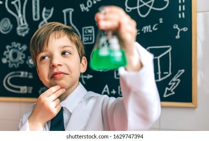 Thoughtful boy dressed as chemist with flask in front of a blackboard with drawings