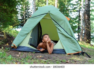 thoughtful boy in forest camping tent