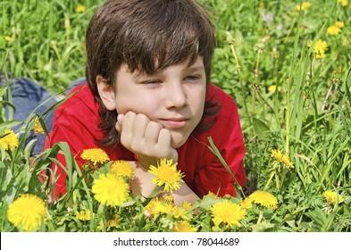thoughtful boy boy lies on a lawn in flowers