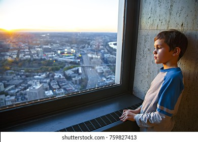 thoughtful boy standing at the window. the child looks at the city from the window of the skyscraper. Copy space for your text
