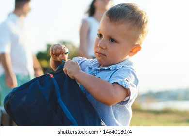 thoughtful boy zipping blue backpack at park