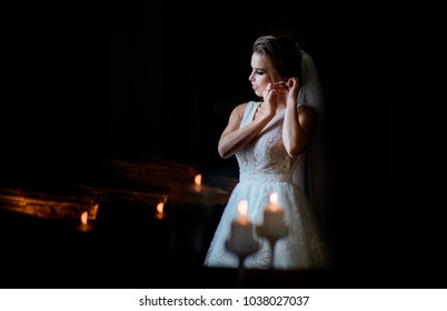 Thoughtful bride stands before a window in dark room with candles