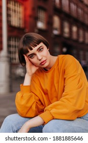 Thoughtful brunette short-haired woman sits outside. Attractive young girl in orange sweatshirt and jeans looks into camera.