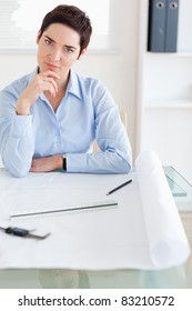 Thoughtful brunette Woman with an architectural plan looking into the camera in an office