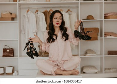 Thoughtful brunette woman in pink pajamas looks at sandals. Lady with red lips poses in dressing room and choose between two pairs of high heels. - Shutterstock ID 1884388417