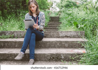 Thoughtful business girl looking to the digital tablet screen while sitting in nature.  Beautiful woman is watching movie on digital tablet, while relaxing after strolling. copy space