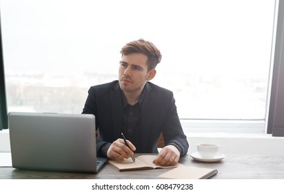 Thoughtful business manager of successful trading company preparing for meeting. Man write notes in notepad and drink coffee in office with big windows. Thinking emotion.