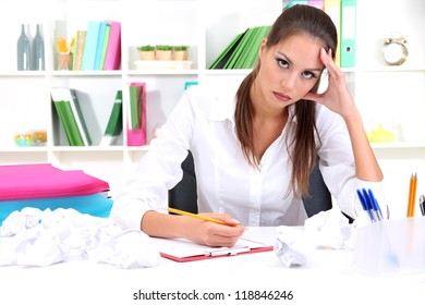 Thoughtful business woman with documents in office