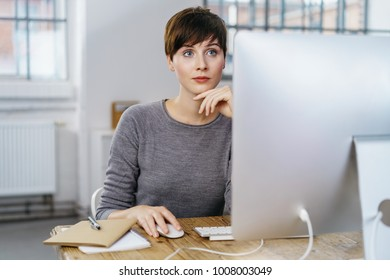 Thoughtful business woman working in office using mouse and looking at monitor.