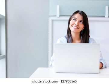 Thoughtful business woman working on a laptop