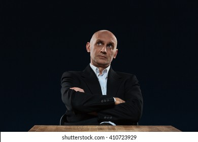 Thoughtful businessman with arms folded sitting at the table over black background