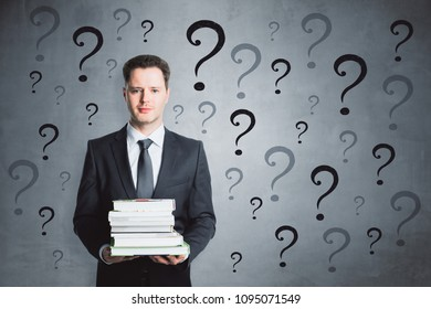 Thoughtful businessman with books and question marks. Confusion and enquiry concept