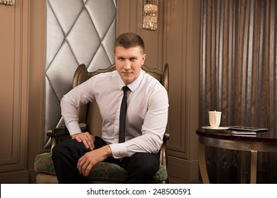 Thoughtful businessman in chic interior. thoughtful young man in a business suit sitting on the armchair with his legs crossed and keeps his hand on his chin
