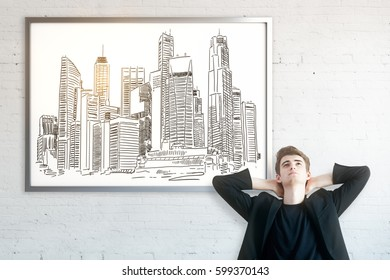 Thoughtful businessman with city sketch in frame. Brick wall background. Engineering concept