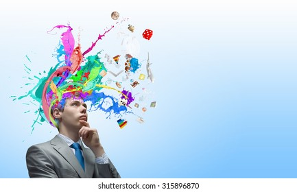 Thoughtful businessman with colorful splashes out of his head