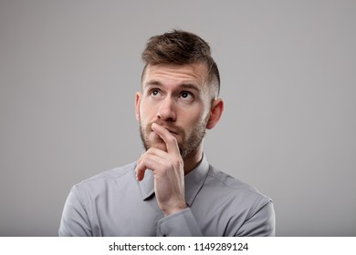 Thoughtful businessman deep in thought with his hand to his chin as he mulls over a problem, plans a new strategy or ponders a new idea