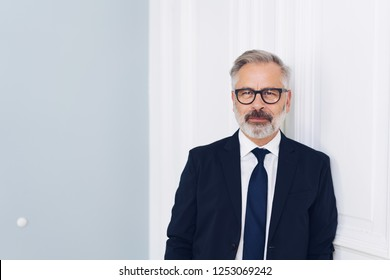 Thoughtful businessman in glasses and suit standing leaning against an interior white wall with copy space staring intently at camera