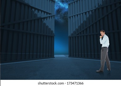 Thoughtful businessman with hand on chin against door opening in dark room
