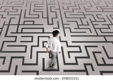 Thoughtful businessman and illustration of maze on light background