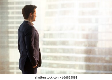 Thoughtful businessman looking at city standing near window, successful entrepreneur considering new opportunity, thinking over business improvement, ways to overcome obstacles, side view, copy space