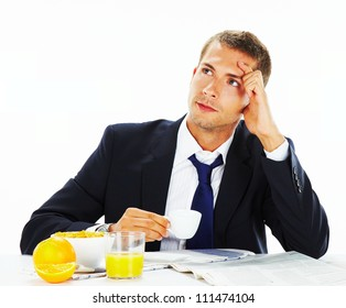 Thoughtful  businessman looking up with concentration and having breakfast