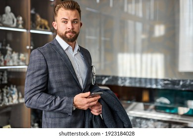thoughtful businessman with mobile phone stand in contemplation, thinking about something, in elegant suit