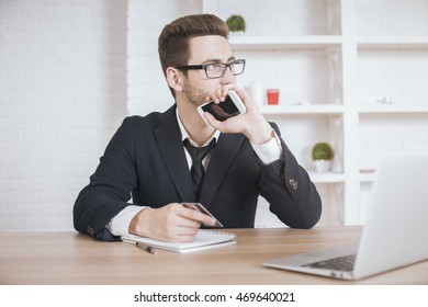 Thoughtful businessman at office desk with laptop holding smartphone and credit card