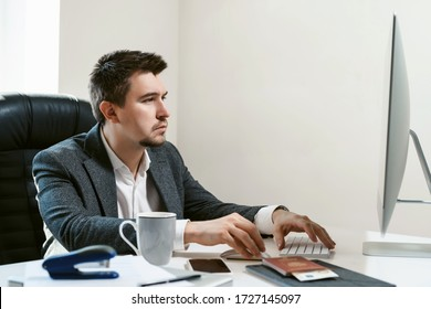 Thoughtful businessman at office workplace is typing text on a desctop computer keyboard. The idea of a new successful project. Financial analyst or IT specialist, sales manager, freelancer.