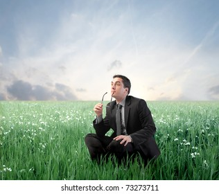 Thoughtful businessman on a green meadow