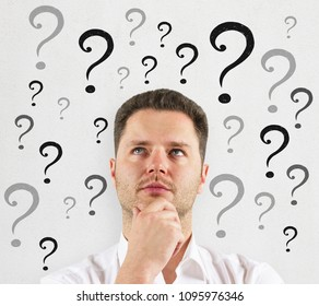 Thoughtful businessman with question marks. Confusion and enquiry concept