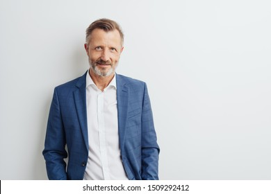 Thoughtful businessman scrutinising the camera with a serious pensive expression against a white studio background with copy space