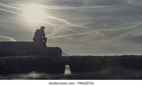 Thoughtful businessman sitting outdoors on a wall silhouetted against the fiery orb of the sun in a colorful sky.