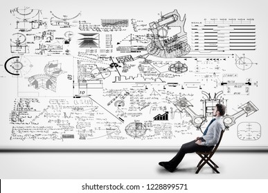 Thoughtful businessman solving math problema drawn on a white wall.