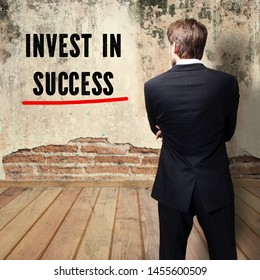 "thoughtful businessman standing in front of a wall with the message ""Invest in success"""