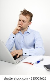 Thoughtful businessman using laptop at desk in office