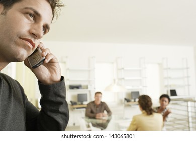 Thoughtful businessman using mobile phone with colleagues discussing in background