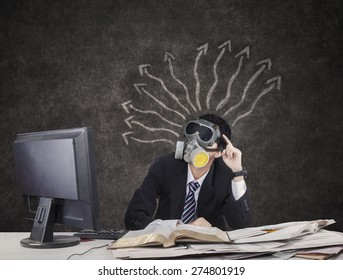 Thoughtful Businessman wearing gas mask with arrows on blackboard