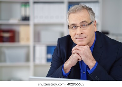 Thoughtful businessman wearing glasses sitting at his desk in the office resting his chin on his hands looking at the camera