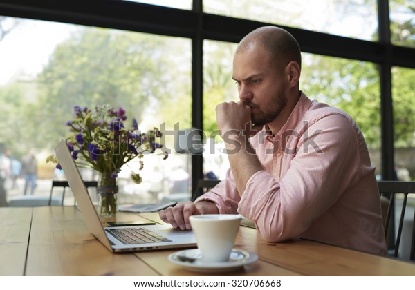 Thoughtful businessman work on net-book while sitting at wooden table in modern coffee shop interior, student reading text or book in cafe, male freelancer connecting to wireless via laptop computer
