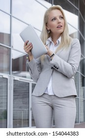 Thoughtful businesswoman holding digital tablet while looking away against office building