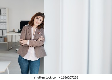 Thoughtful businesswoman looking at the camera as she relaxes leaning against an interior wall alongside a window in the office with folded arms