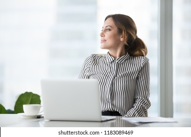 Thoughtful businesswoman looking to side dreaming about future success, smiling female boss or ceo distracted from work thinking about something, looking through window of modern office building