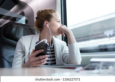 Thoughtful businesswoman looking trough the window, listening to podcast on cellphone using headphone set while traveling by train in business class seat.