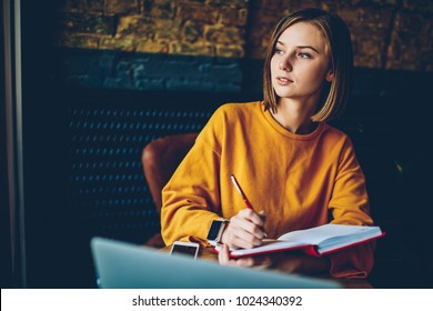Thoughtful businesswoman pondering on strategy for design project making research in notebook.Contemplative student doing homework task solving problems and analyzing information in cafe interior