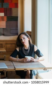 Thoughtful businesswoman sitting at cafe table