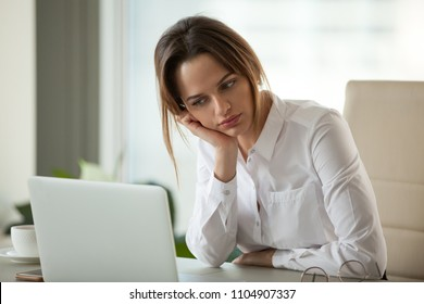 Thoughtful businesswoman thinking searching new ideas looking at laptop, serious employee feeling bored with dull monotonous online office work, employee disinterested in doing boring computer task